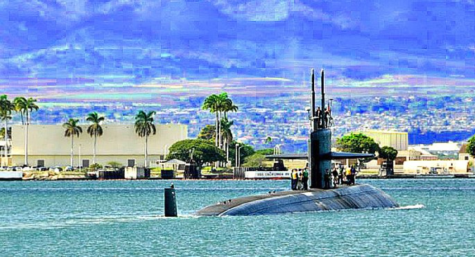 Submarine in Pearl Harbor, Hawaii with agua-colored water and beautiful backdrop of mountains.